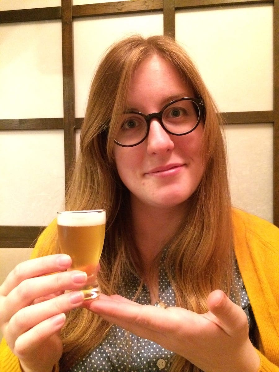 A photograph of a woman, Erin, presenting her unusually small glass of beer at a restaurant in Japan.